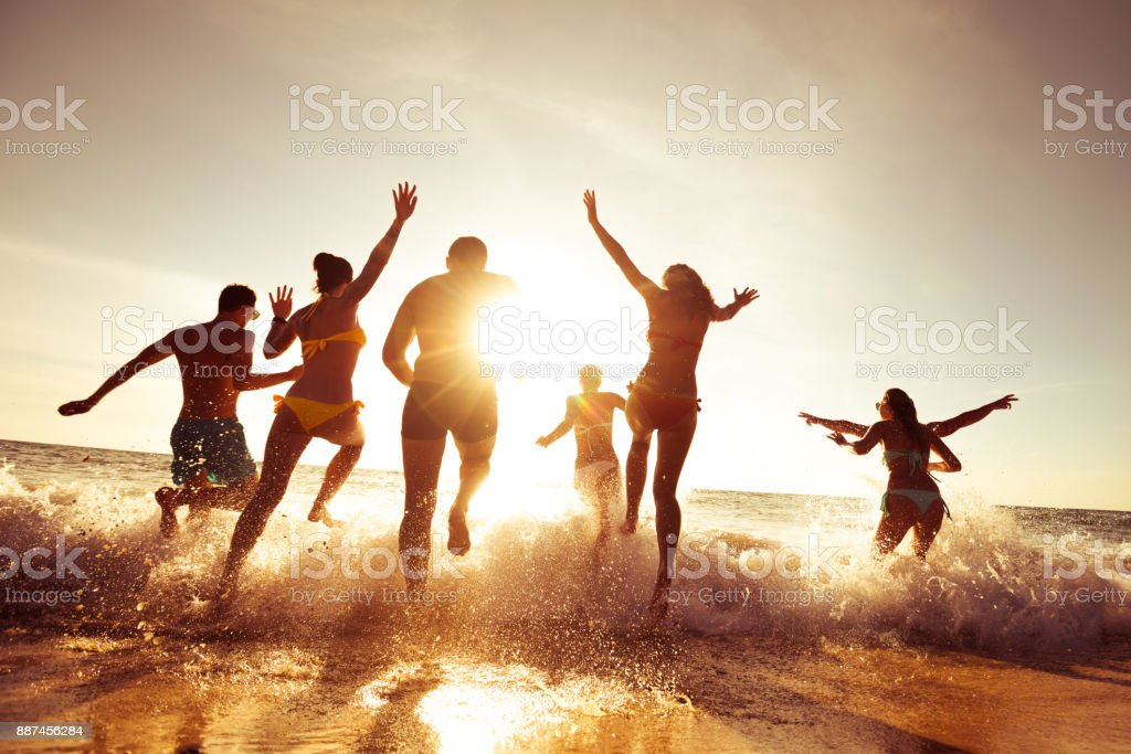 Big company of friends having fun at sunset beach stock photo