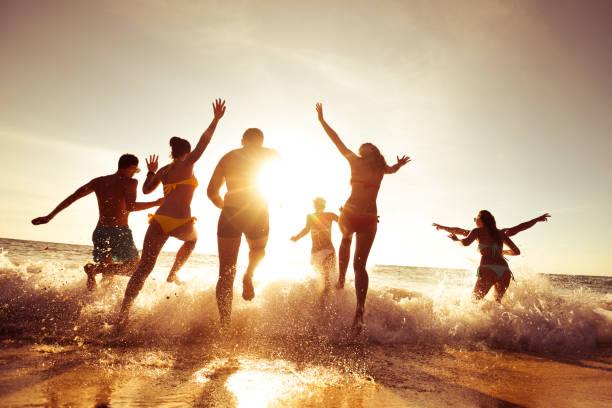 grote gezelschap van vrienden plezier op sunset beach - strandfeest stockfoto's en -beelden