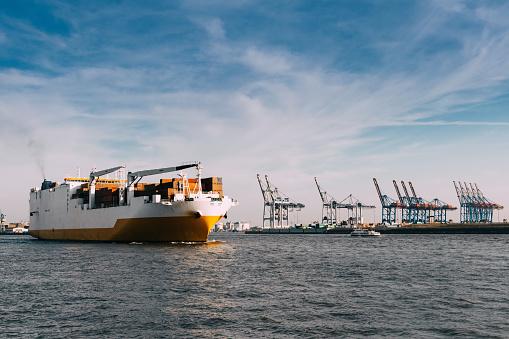 big cargo ship on Elbe River in Hamburg port under blue sky