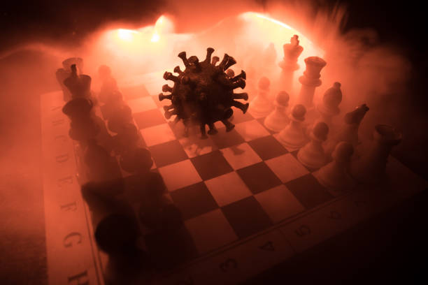 Big Corona virus miniature model on chessboard with fog and backlight. Creative artwork decoration. Selective focus – zdjęcie