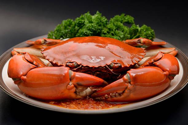 big crab on plate in singapore restaurant - krab gerecht stockfoto's en -beelden