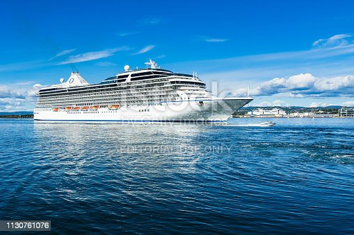 A big cruise ship overtaken by a speedboat in Oslo fjord. Oslo, Norway, August 2018