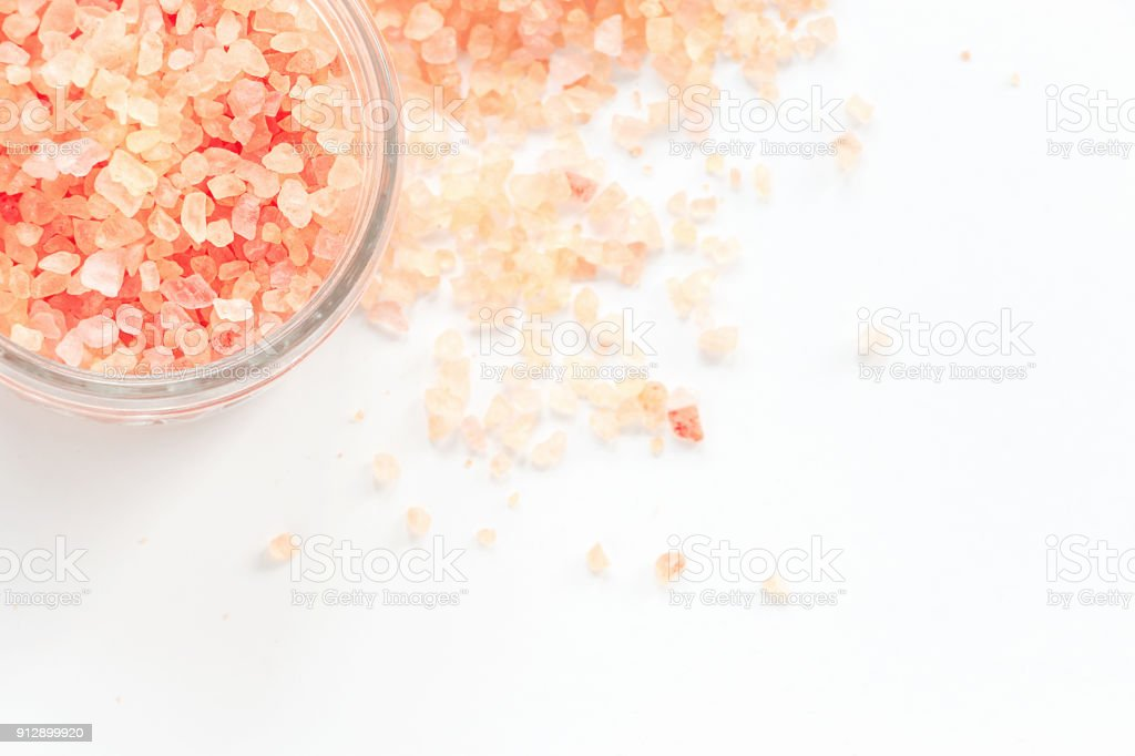 Big Crystals of pink Himalayan salt in jar. White background. Top view. Isolated. stock photo