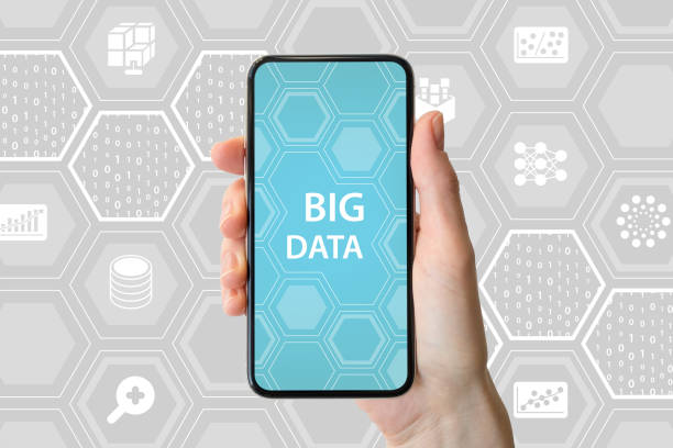 Big data concept. Hand holding modern bezel-free smartphone in front of neutral background with icons stock photo
