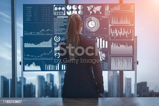 Business analyst marketer look at big data report on computer screen analyzing and research global stock market exchange trend. Concept of futuristic information technology for business decision make.