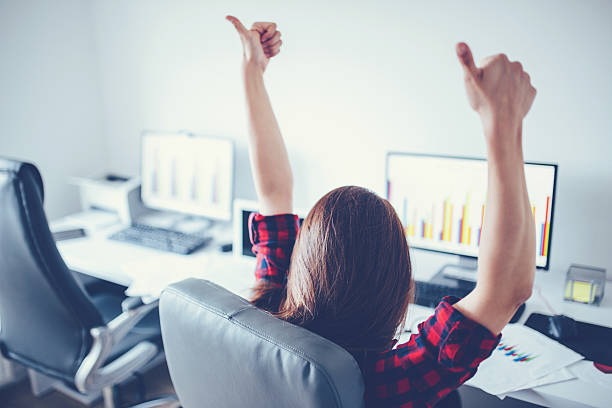 Big deal Portrait of happy young successful businesswoman celebrate something with arms up. Happy woman sit at office and look at Computer/ laptop. Positive emotion. Big deal, promotion, lottery win or discount concept perks stock pictures, royalty-free photos & images