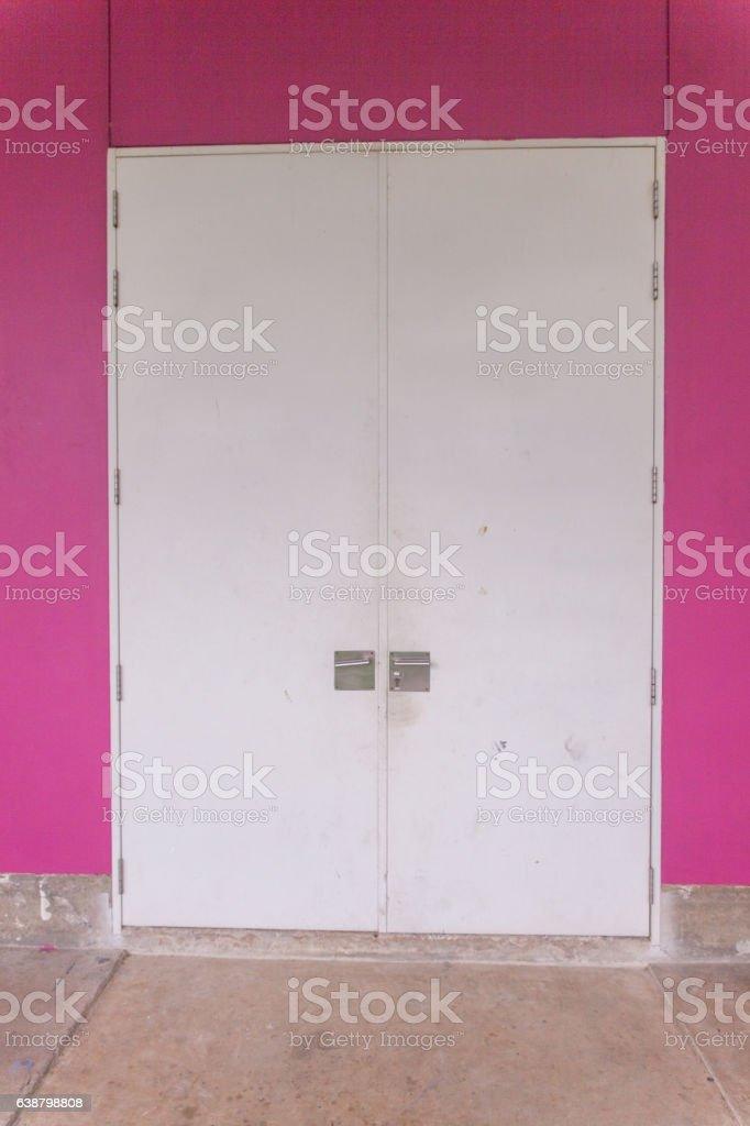 Big door and pink concrete wall stock photo