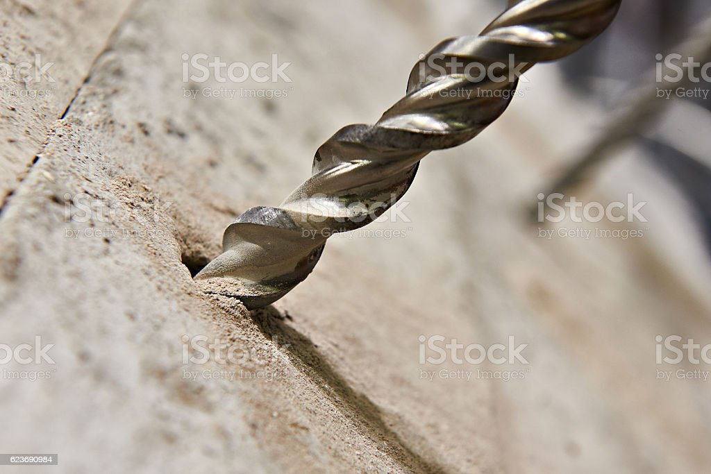 Big drill bit in hole of concrete stock photo