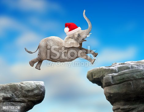 istock Big Elephant as a Santa jumping over a gap. Successful business metaphor and jump to new year concept. 863753128