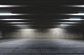 A big open empty parking garage under the lights in the dark area.