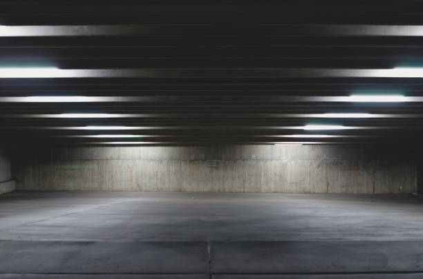 A big empty parking garage under the lights A big open empty parking garage under the lights in the dark area. vanishing point stock pictures, royalty-free photos & images