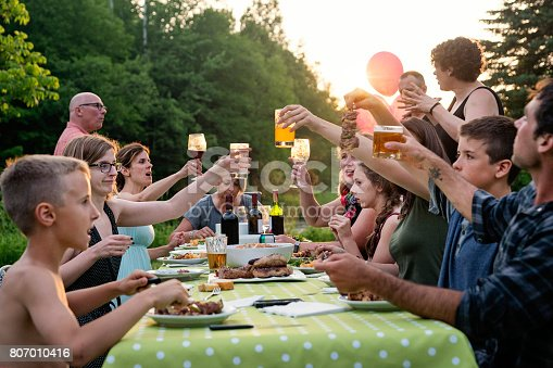 istock Big family barbecue gathering at sunset, summer outdoors. 807010416