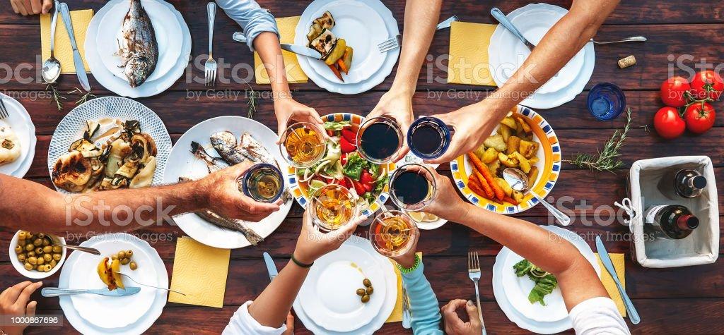 Großes Familienessen. Vertikale Ansicht von oben am Tisch serviert und die Hände mit klirrendes Kelche – Foto