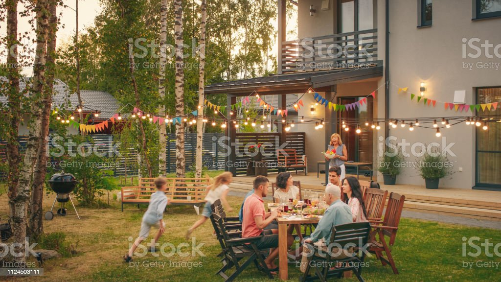 Big Family Garden Party Celebration, Gathered Together at the Table Family, Friends and Children. People are Drinking, Passing Dishes, Joking and Having Fun. Kids Run Around Table. royalty-free stock photo