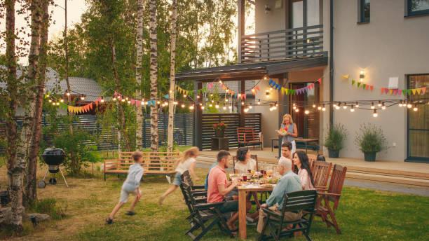 grande festa in giardino per famiglie, riunita al tavolo famiglia, amici e bambini. le persone bevono, passano piatti, scherzano e si divertono. i bambini corrono intorno al tavolo. - family foto e immagini stock