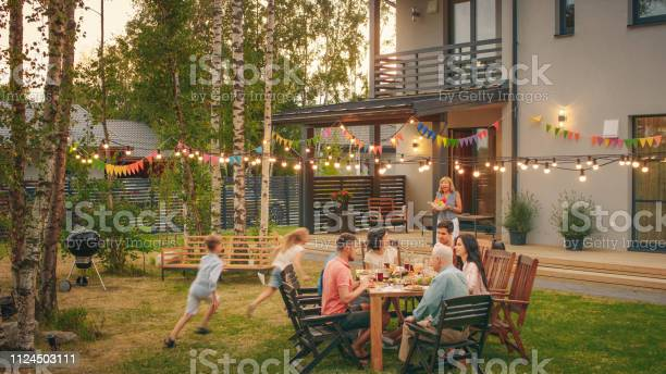 Photo of Big Family Garden Party Celebration, Gathered Together at the Table Family, Friends and Children. People are Drinking, Passing Dishes, Joking and Having Fun. Kids Run Around Table.