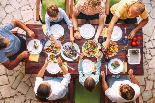 große familie haben ein abendessen mit frisch gekochte mahlzeit auf offene terrasse im garten - kindergrill stock-fotos und bilder