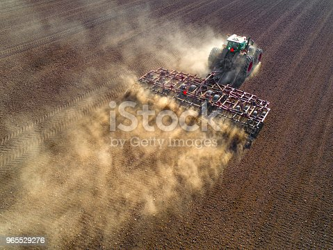 Big farm tractor tilling dusty Springtime fields, aerial view.