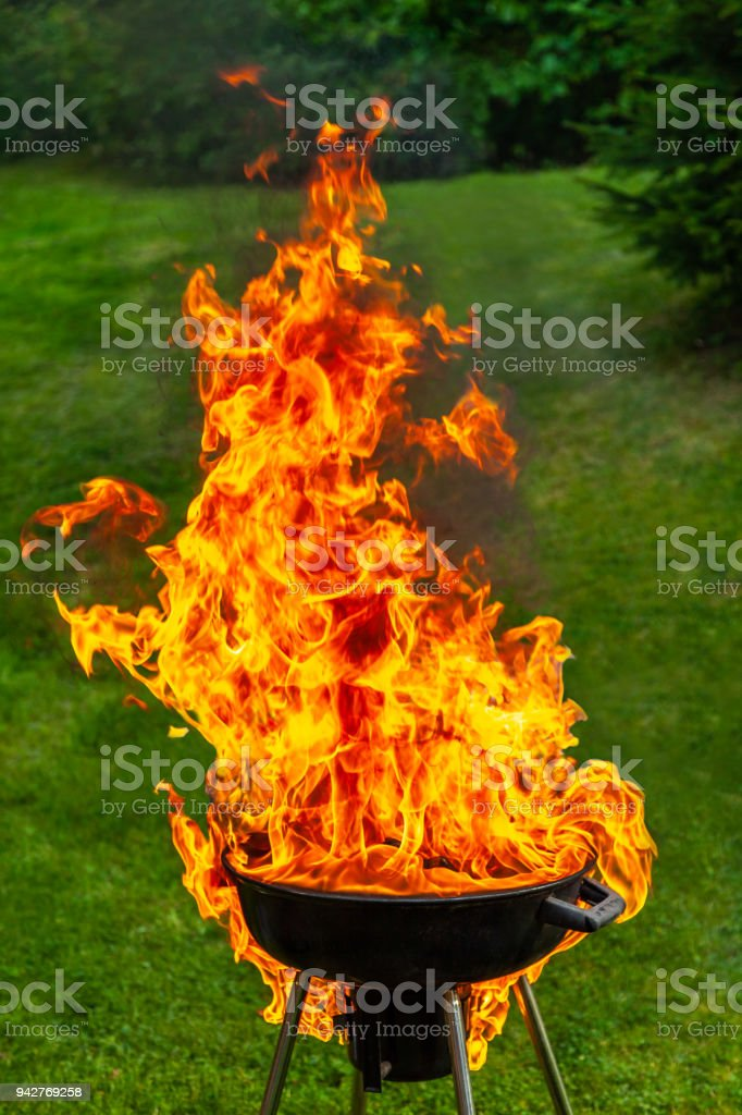 A big fire flashover a black grill outdoors when having a barbecue. royalty-free stock photo