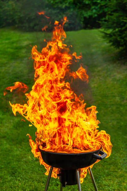 A big fire flashover a black grill outdoors when having a barbecue. stock photo