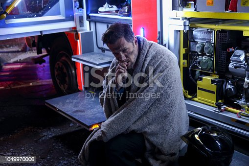 Man with blanket sitting at firemen truck. Black from smoke and fire.