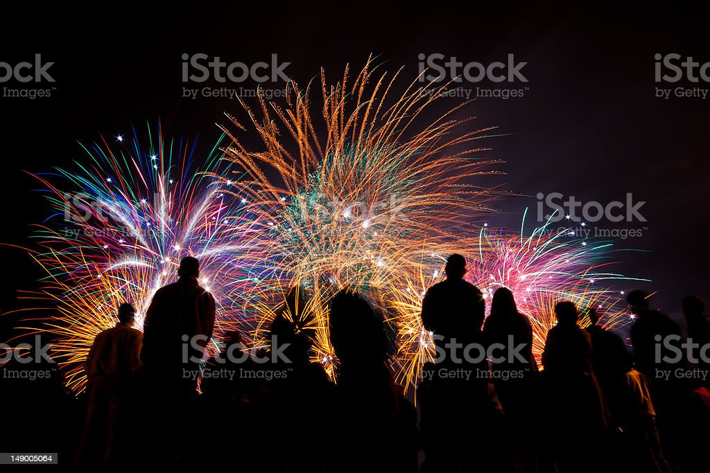 Big fireworks with silhouetted people in the foreground watching stock photo