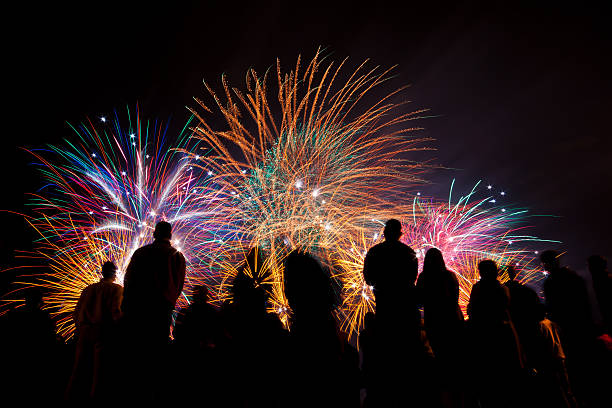big fireworks with silhouetted people in the foreground watching - fireworks stock pictures, royalty-free photos & images