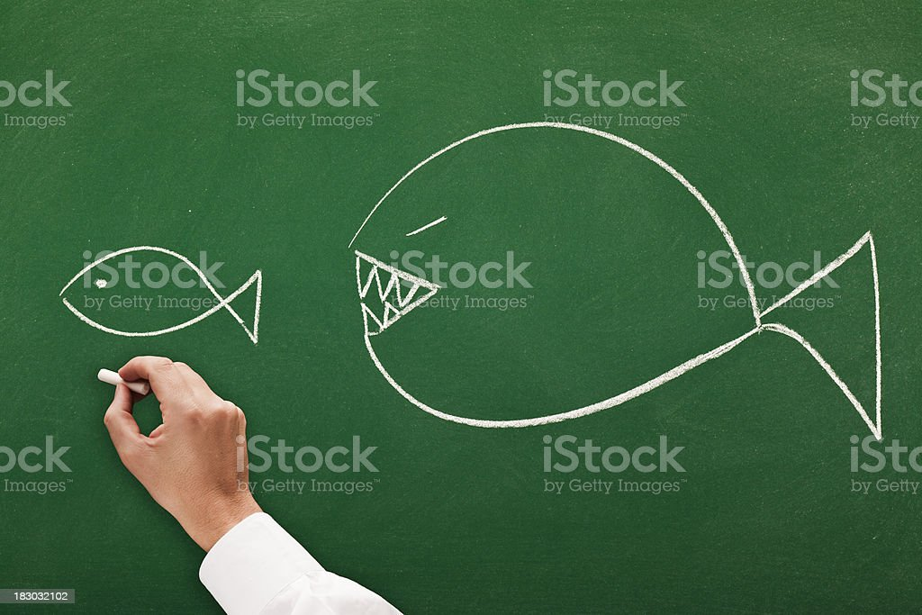 big fish eats small one stock photo
