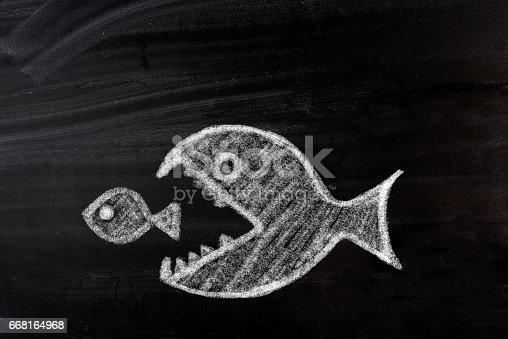 istock Big fish eats small one 668164968