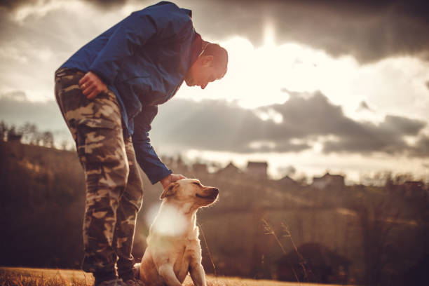 Big friendship A man and a dog are big friends. The man is wearing blue jacket and is enjoying his spare time with his dog. He is caressing the dog animal hand stock pictures, royalty-free photos & images
