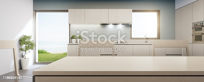 665910118istockphoto Big glass window near counter and cabinet of modern sea view kitchen in luxury summer beach house. 1186634142