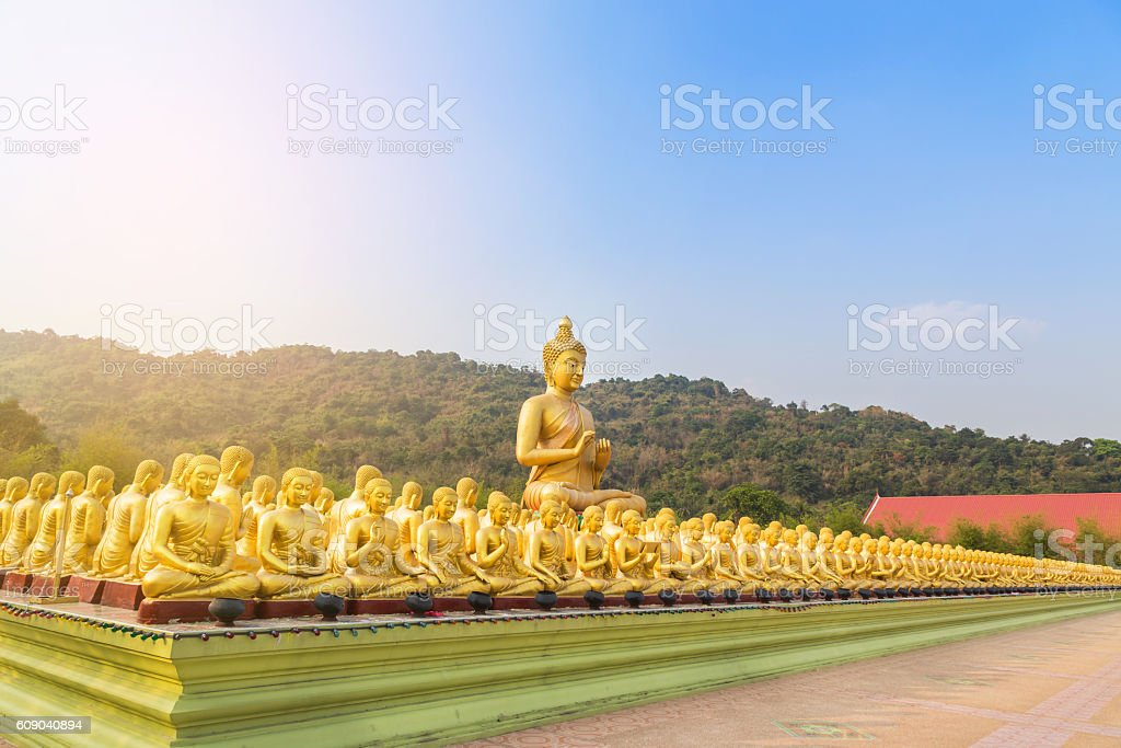 big golden buddha statue and many small golden buddha statues in temple stock photo