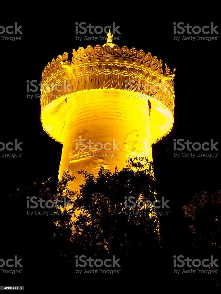 Big golden prayer wheel at night stock photo