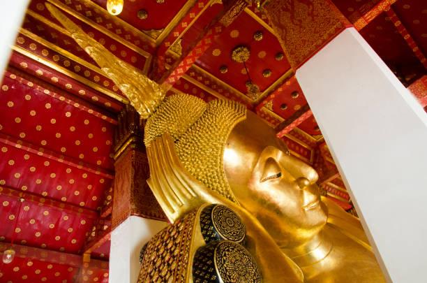 big golden reclining buddha statue in ubosot or chapel - ruhegebet tattoo stock-fotos und bilder