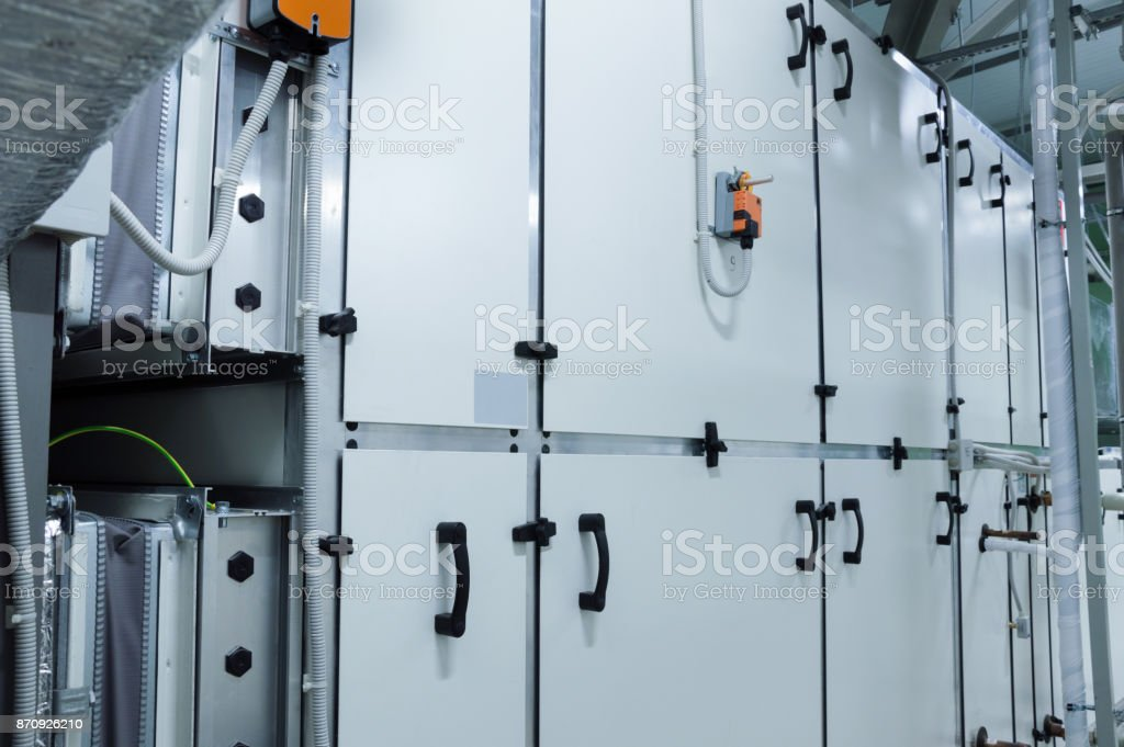 Big gray commercial air conditioner in the ventilation plant room stock photo