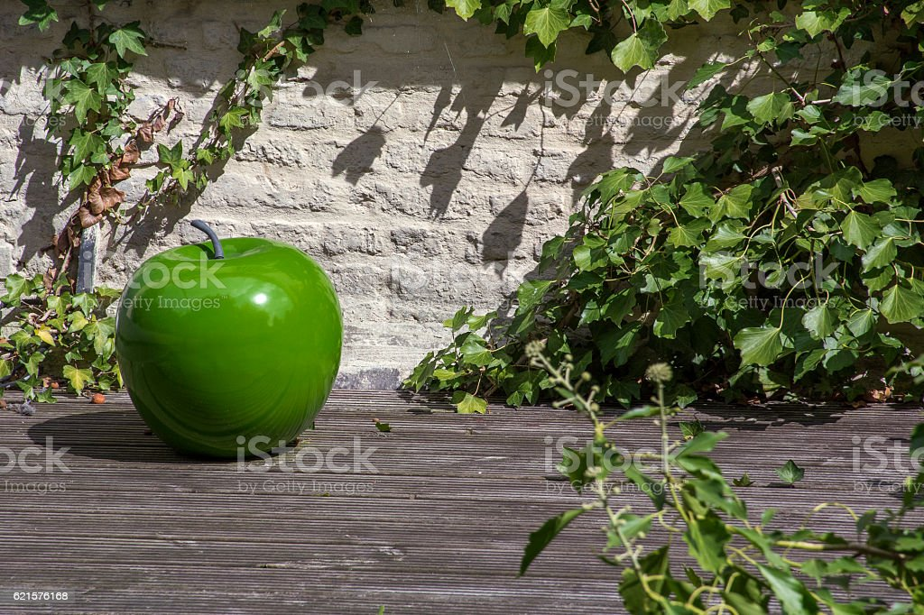 Big green artificial apple on the stand with leaves photo libre de droits