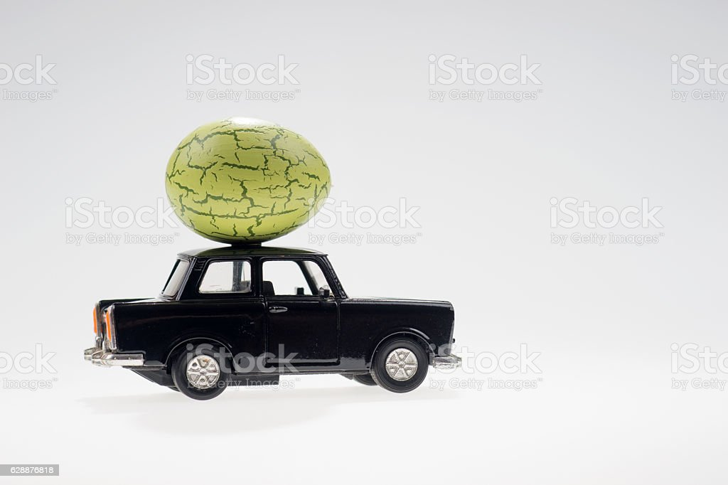Big green easter egg on the black car stock photo