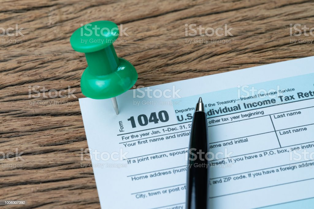 Big Green Thumbtack Pin On 1040 Individual Income Tax Form With Pen