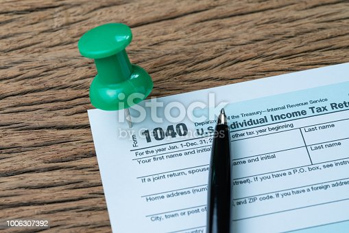 Big green thumbtack pin on 1040 individual income tax form with pen to fill in, reminder for yearly submission for US internal revenue service department.