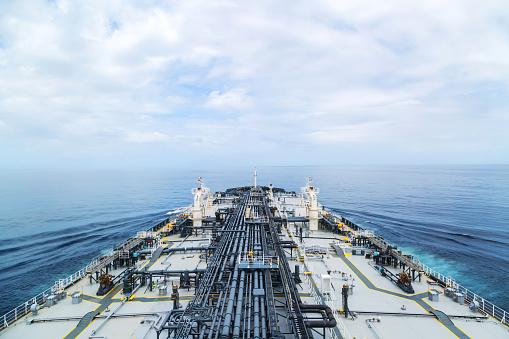 Big grey oil tanker underway in the open blue sea.