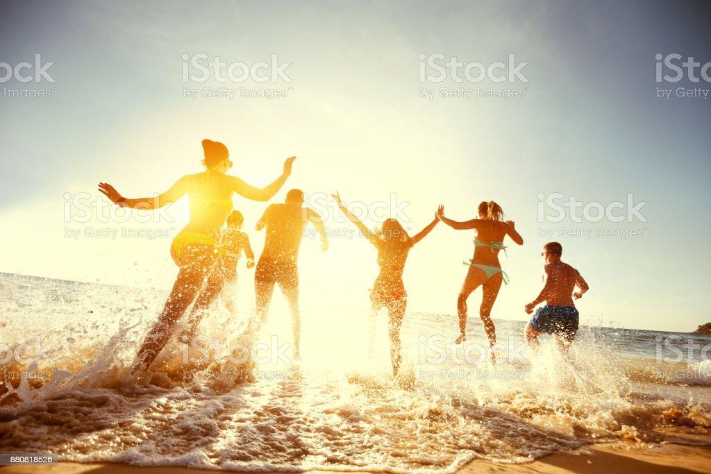 Grupo amigos del atardecer playa ejecutar - foto de stock