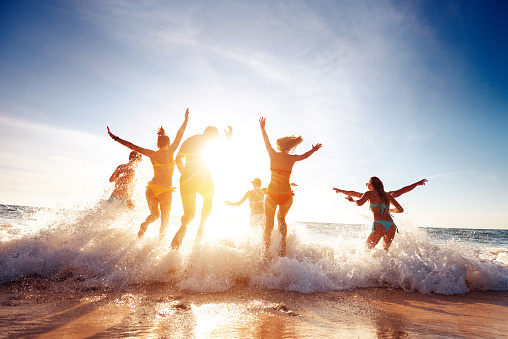 Big group happy friends runs and having fun at sunset beach