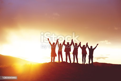 Big group of happy friends with raised hands at sunset. People's silhouettes. Unity, success, team or friendship concept