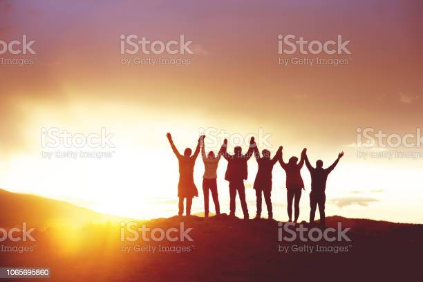 Photo of Big group happy people's silhouettes success raised hands