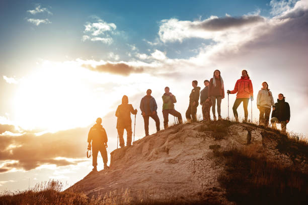 Big group of hikers against sunset