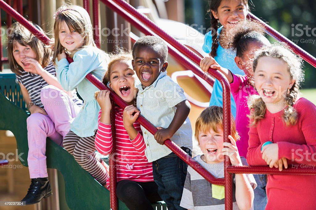 Big group of multi-ethnic children on a sunny playground stock photo