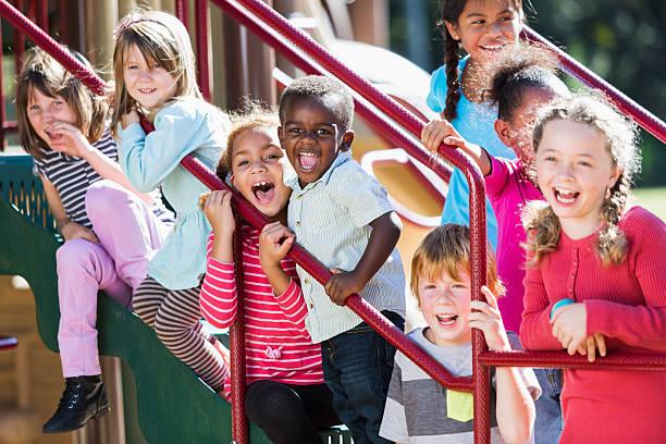 gran grupo multiétnico en la soleada patio de juegos para niños - patio de colegio fotografías e imágenes de stock