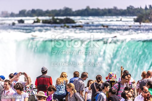 Toronto, Canada - Aug 21st 2017 - Big group of people in the foreground looking to the Niagara Falls in a summer hot day in Canada