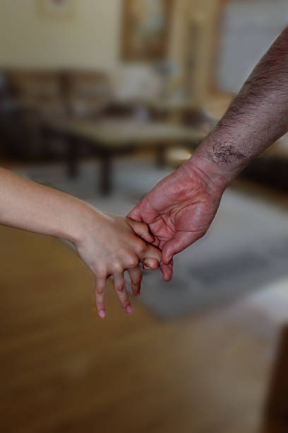 Big, hairy man's hand is pulling small, girl's hand. stock photo