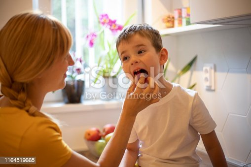 Young woman feeding her four years old son with fresh raspberries.